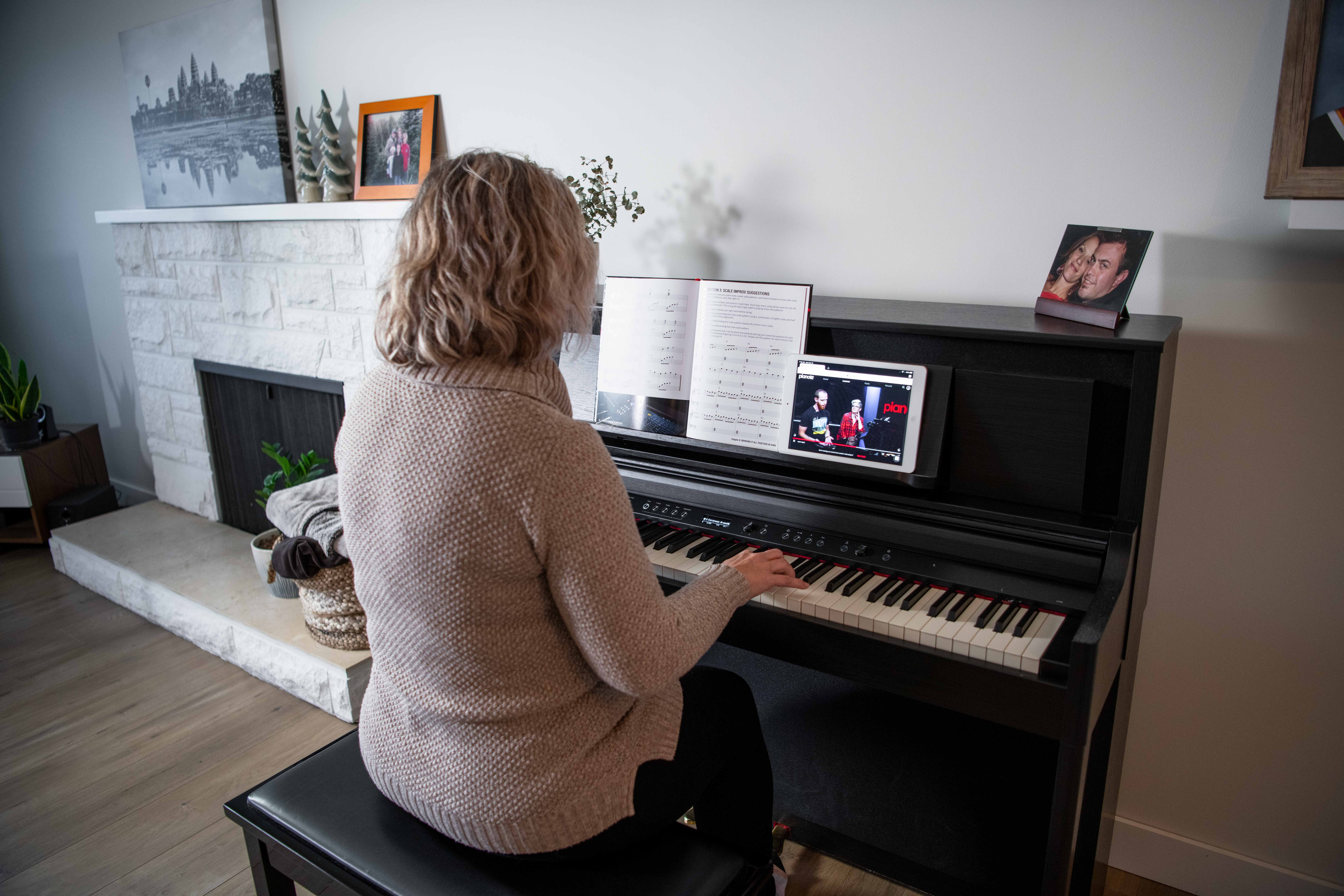 Woman playing console keyboard (upright piano) at home with book and iPad.