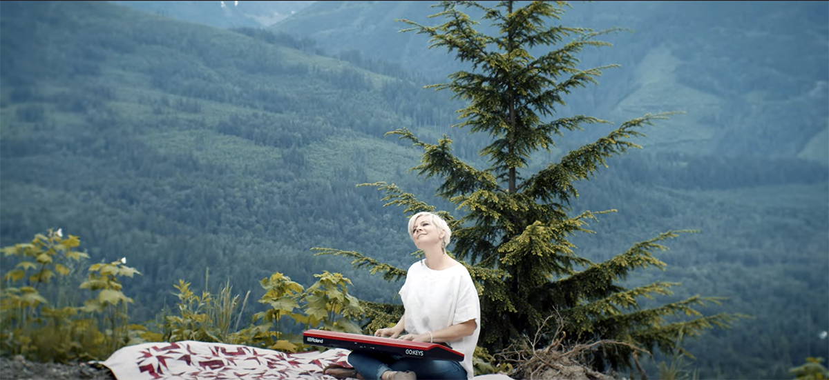 Lisa sitting on picnic blanket with keyboard on lap in front of a mountain background.