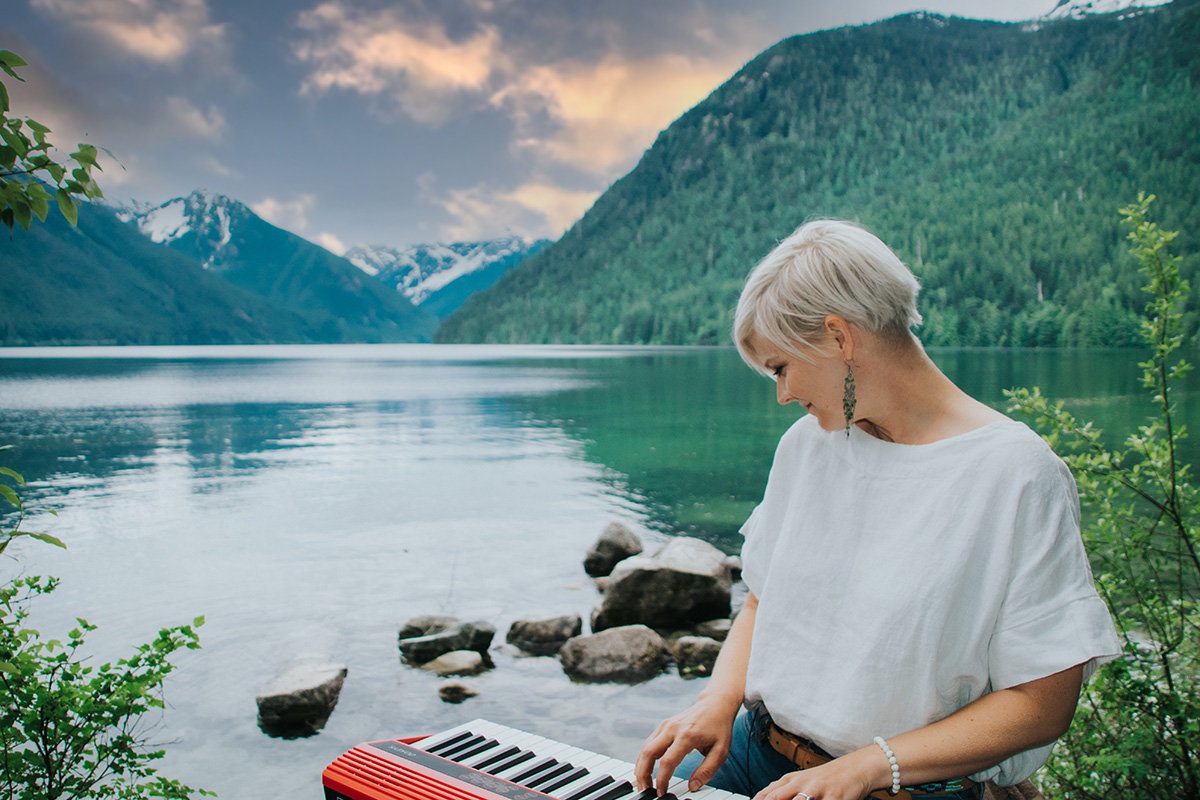 Lisa with keyboard on lap looking behind her at a beautiful lake.