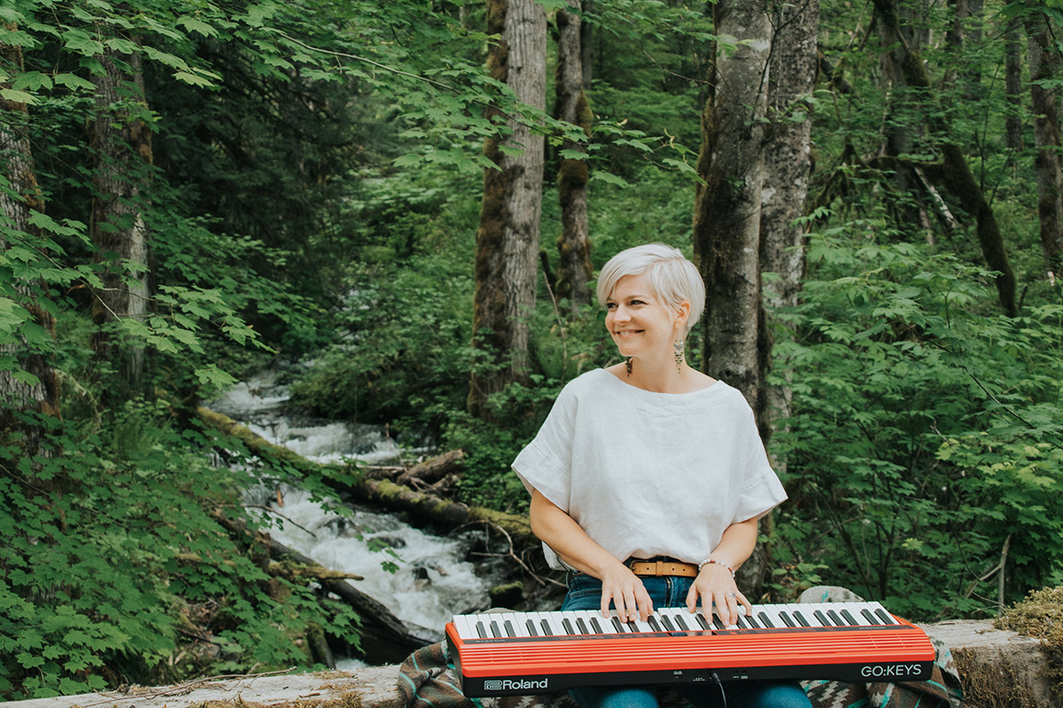 Lisa sitting on log with keyboard on lap with small waterfall in the background.