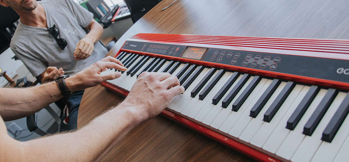 Angled photo of hands playing red keyboard on table.