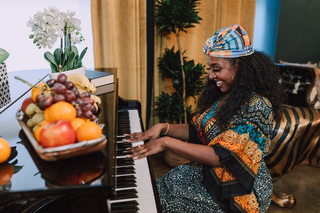 Happy woman in colorful dress with hands on piano with tray of fruit and flowers on top.