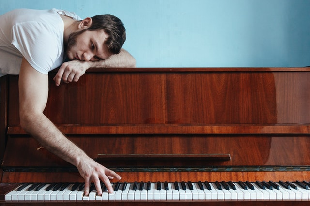 Man leaning on top of upright piano with bored expression reaching down to play keys.