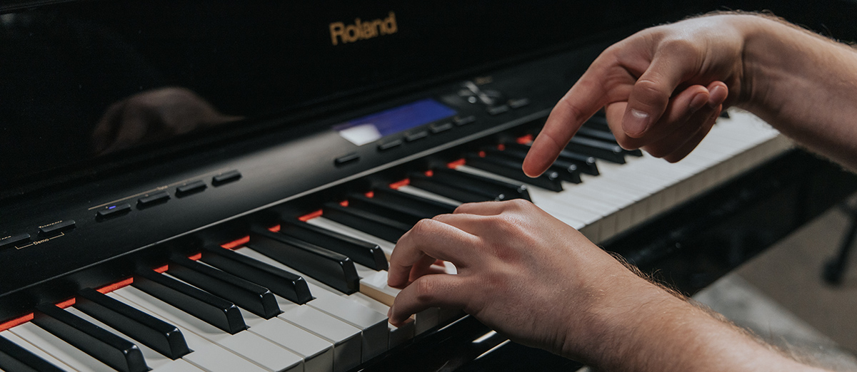 Closeup of hands on piano with one hand pointing at keyboard.