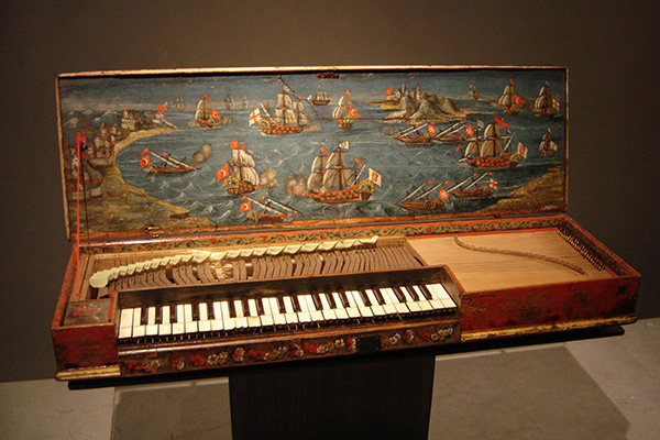 Old, wooden clavichord displayed in a museum with a painting of ships on the inside of the lid.