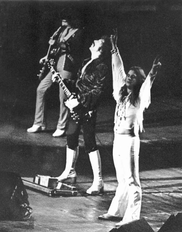 Black Sabbath on stage - black and white photo. Man in white (Ozzy) raising his arms.