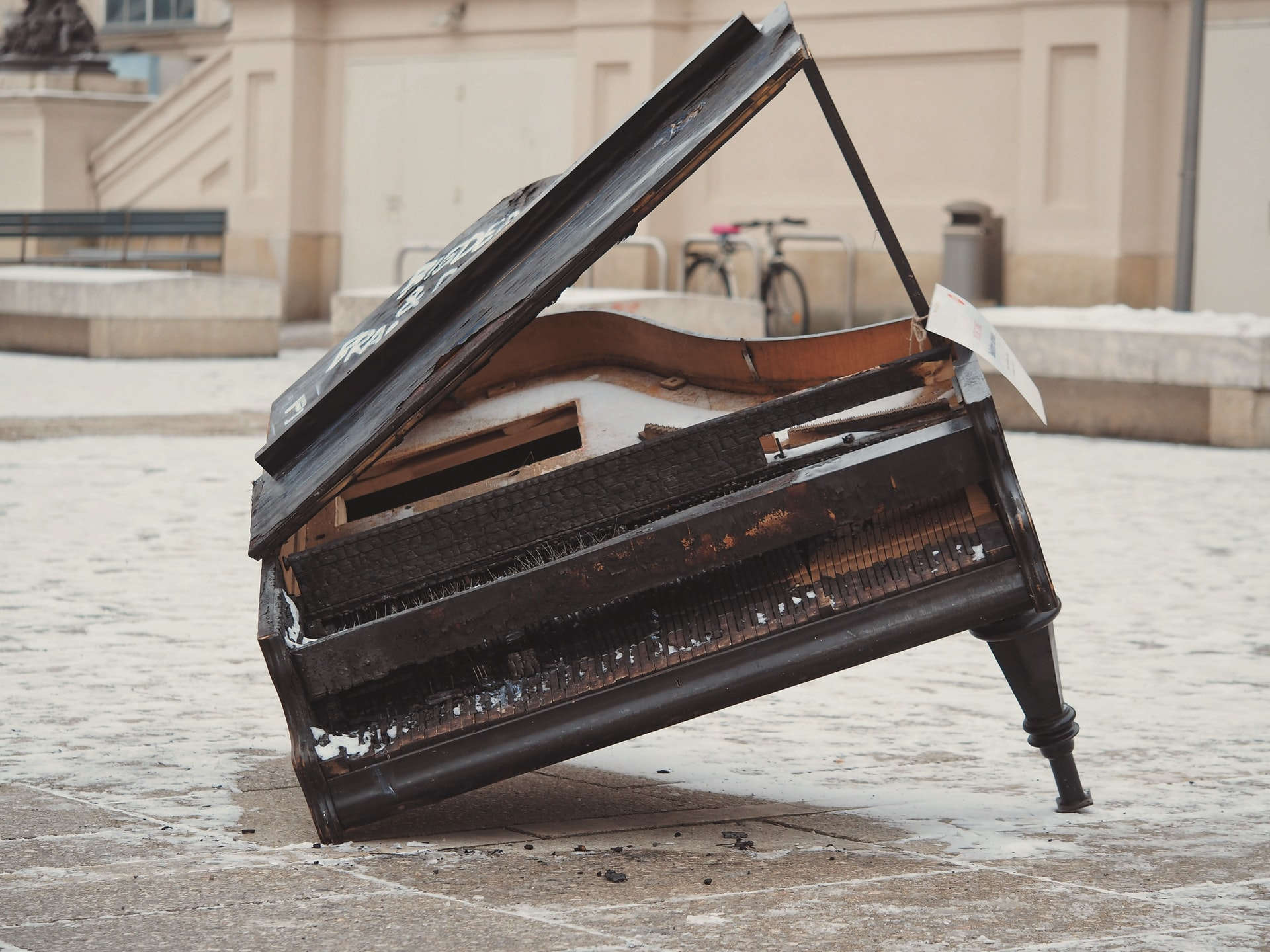 A very old broken, burnt grand piano with graffiti and a broken leg, laying on an angle.