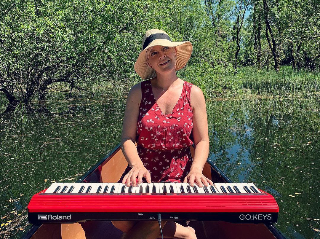 Lisa playing red Roland GO:KEYS while sitting in a canoe in the water.