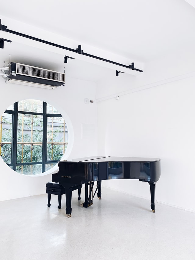 Closed lid grand piano in white spacious room with circular window.