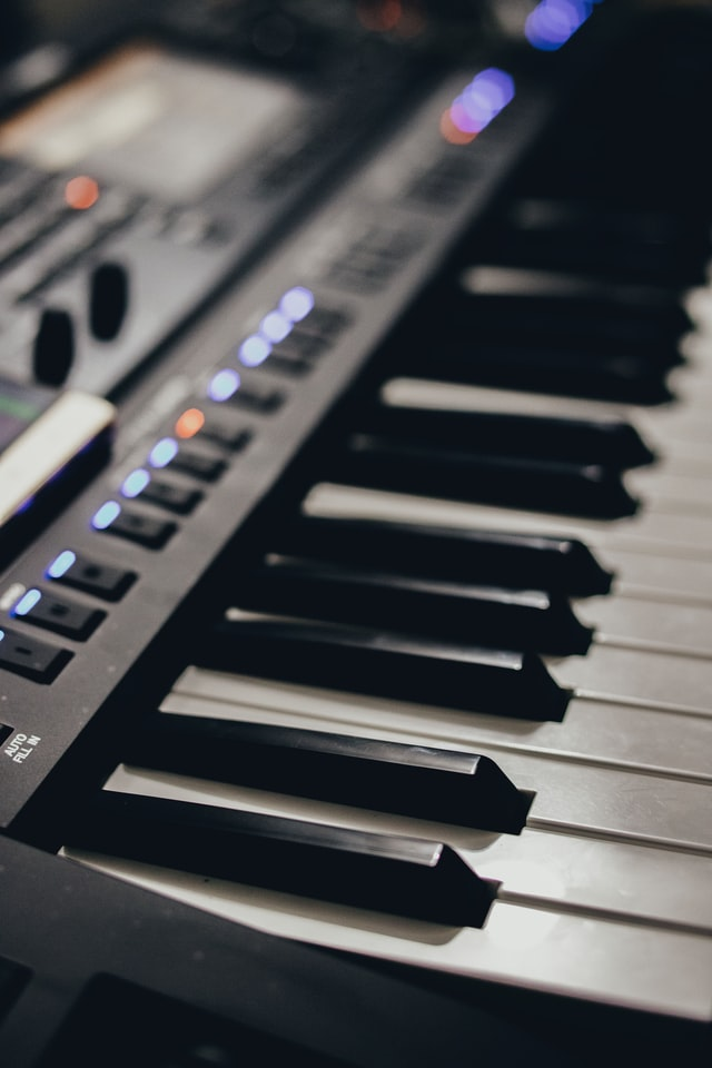 Close up view of synthesizer keyboard with controls.