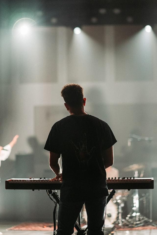 Behind a man, backlit, playing slab keyboard while standing.