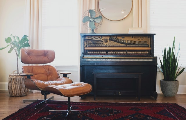 Eames chair next to antique upright with strings showing and a fan on top.