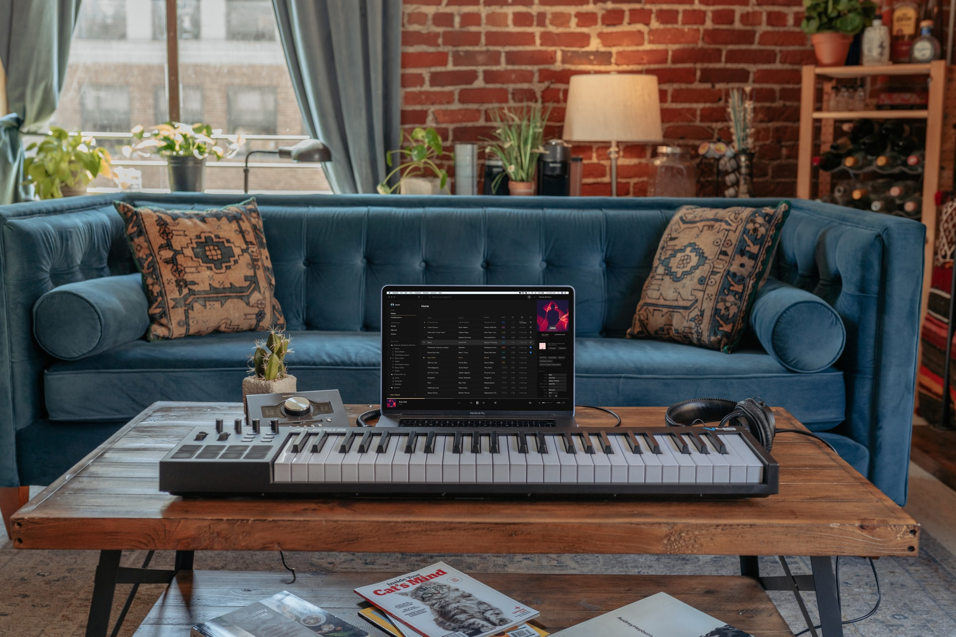 Synthesizer keyboard and laptop on a coffee table in front of a couch in a cozy, wood and exposed brick home.