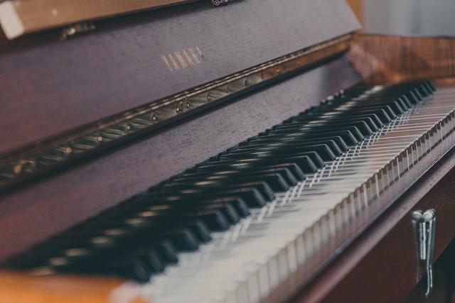 Close up of keyboard of a slightly worn Yamaha upright piano.