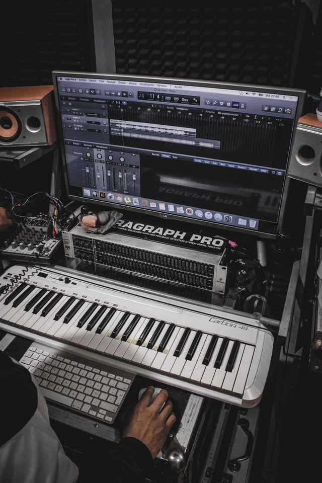 Midi keyboard in front of a computer screen displaying a digital audio workstation.