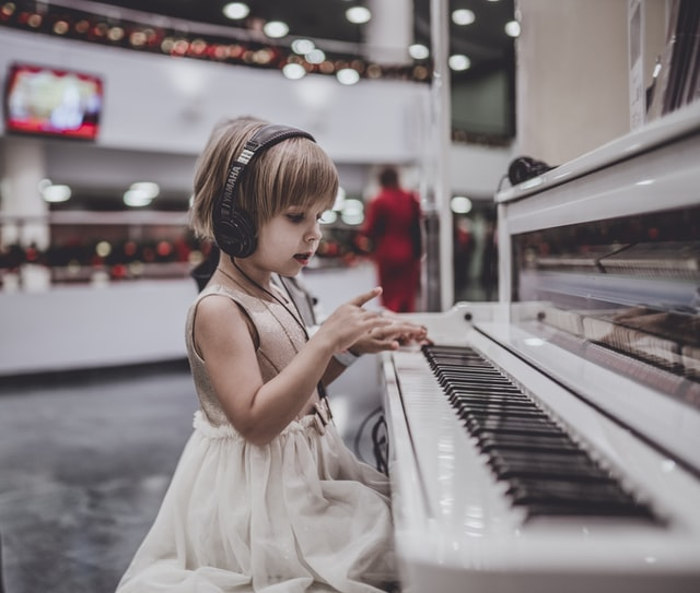 Child with headphones plays see-through white piano in a store.