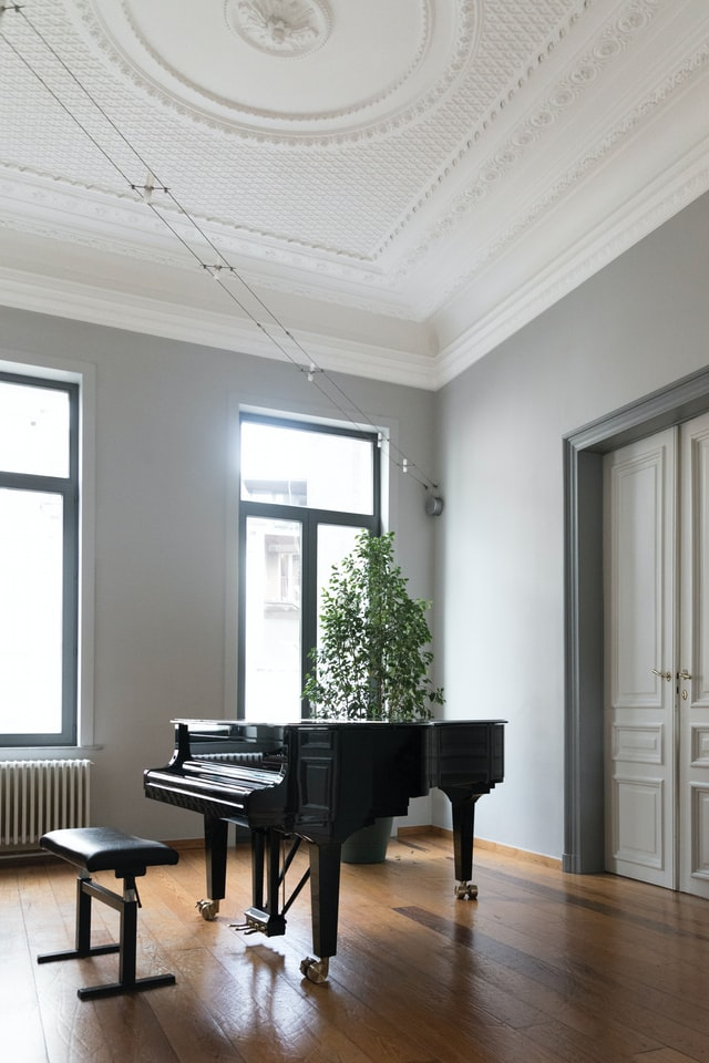 Grand piano with lid and fallboard closed in a high-celing room.