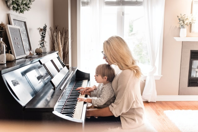 Woman with long blonde hair playing piano with child on her lap.