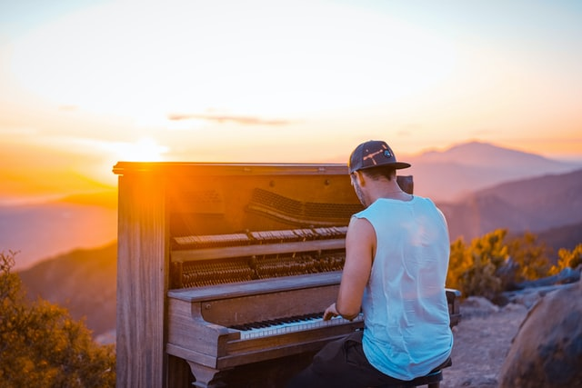 Man in tank top and backwards hat plays upright piano on a mountain overlooking a sunset view.