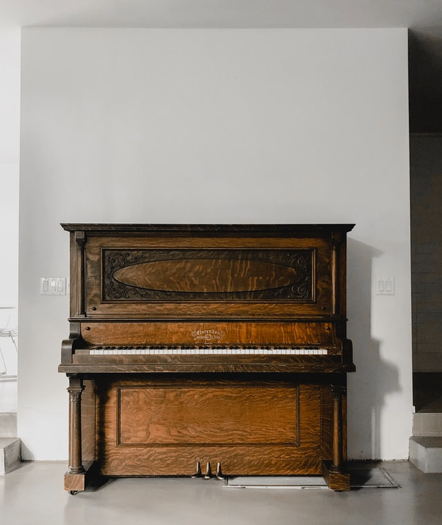 Upright piano in wood finish in white, empty room against wall.