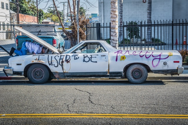 """An old white pick-up with graffiti """"I used to be pretty."""""""