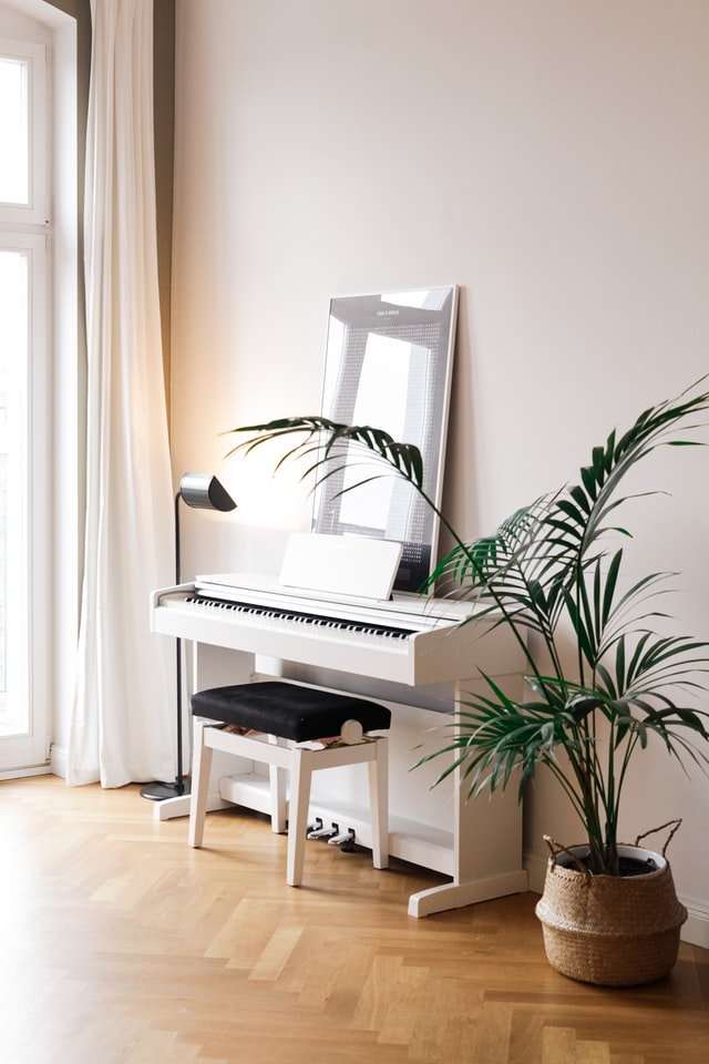 White console digtal piano in a clean room with floor plant.