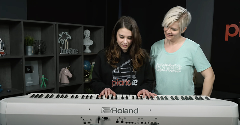Kaitlyn and Lisa in front of white Roland FP90X.