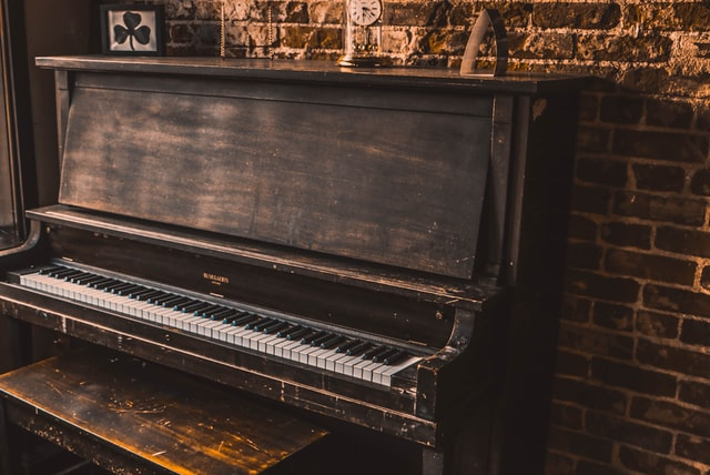 An old, slightly worn upright piano in wood finish.