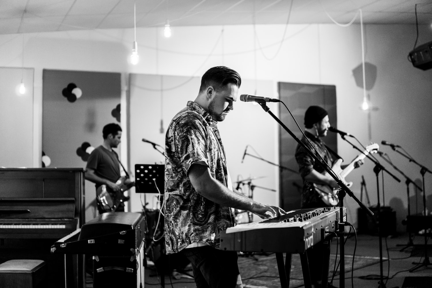 Black and white photo of band playing with keyboardist in the foreground. Man in flowery shirt plays Nord keyboard with bassist and guitarist.