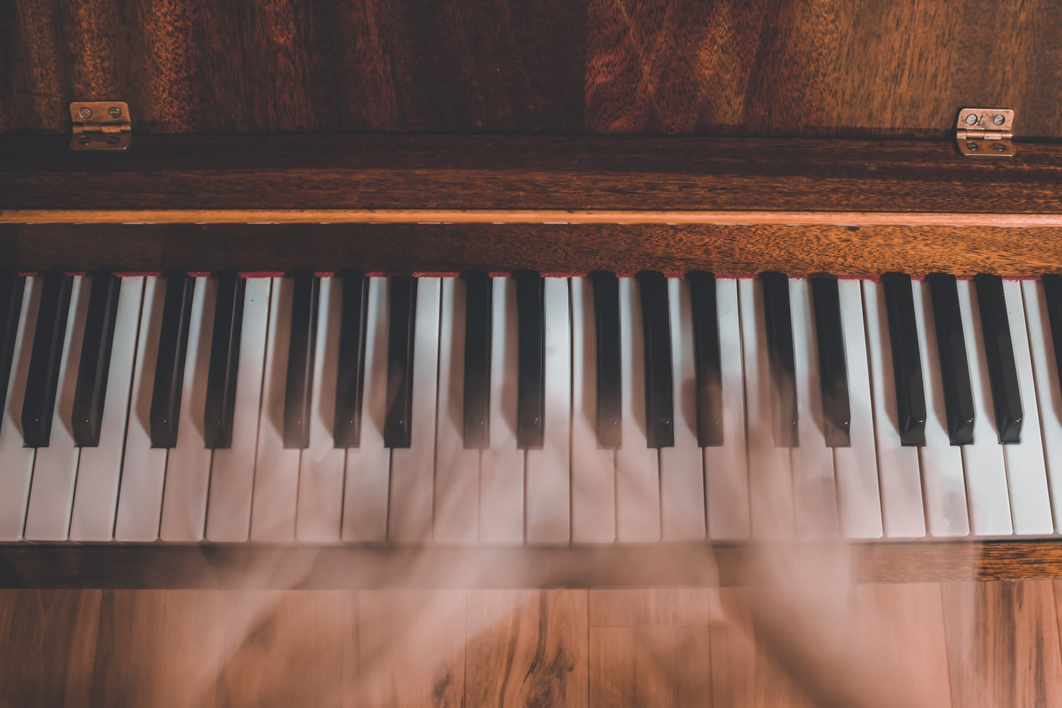 Bird's eye view of piano keyboard in wood finish with blurry hands.