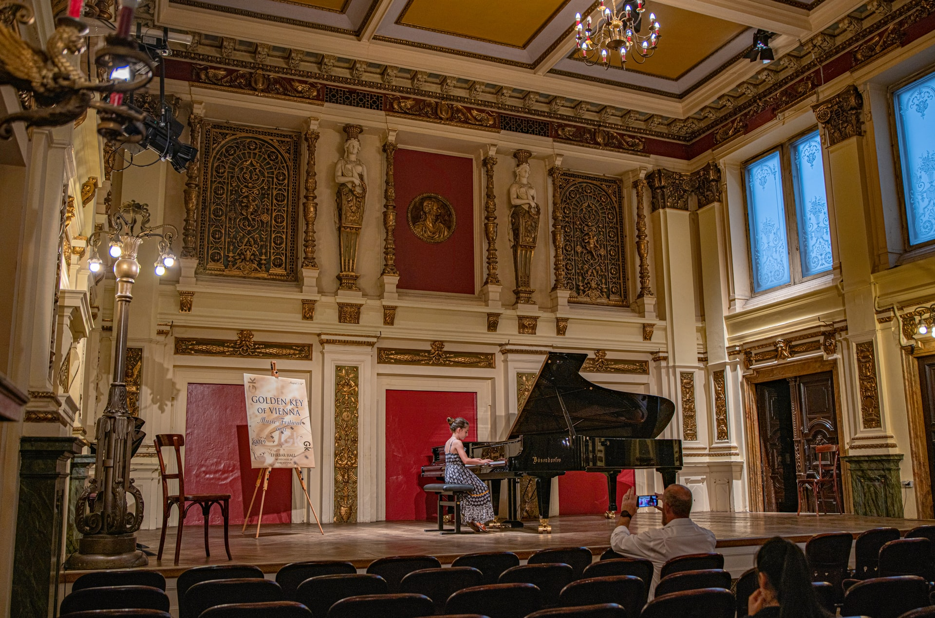 Woman plays grand piano in ornate old gold gilded room.