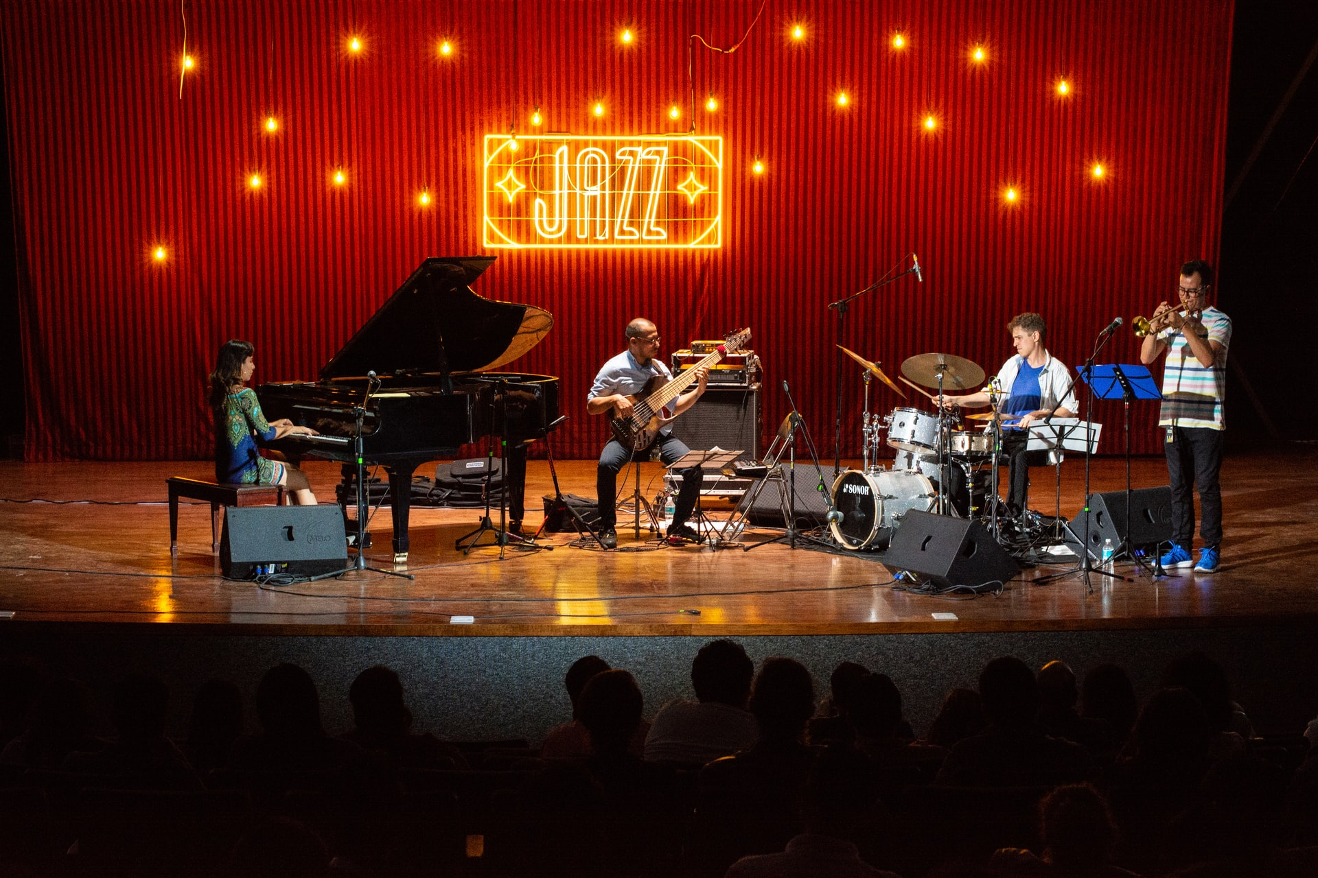 """Jazz band playing on stage with red light sign """"JAZZ"""" behind them. Left to right: woman playing grand piano, man playing bass, man playing drums, man playing trumpet."""