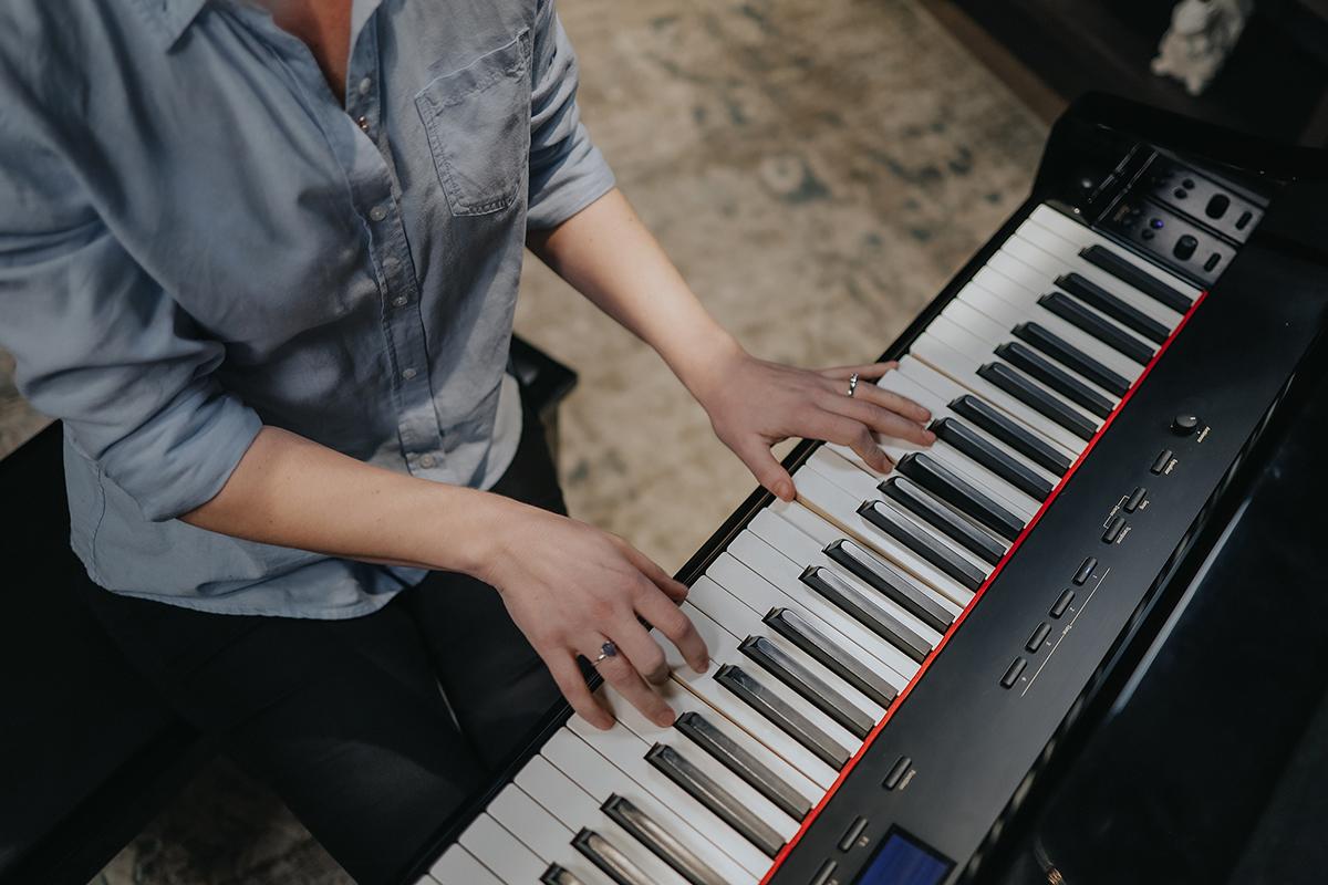 Bird's eye view at an angle of Lisa playing on studio piano.