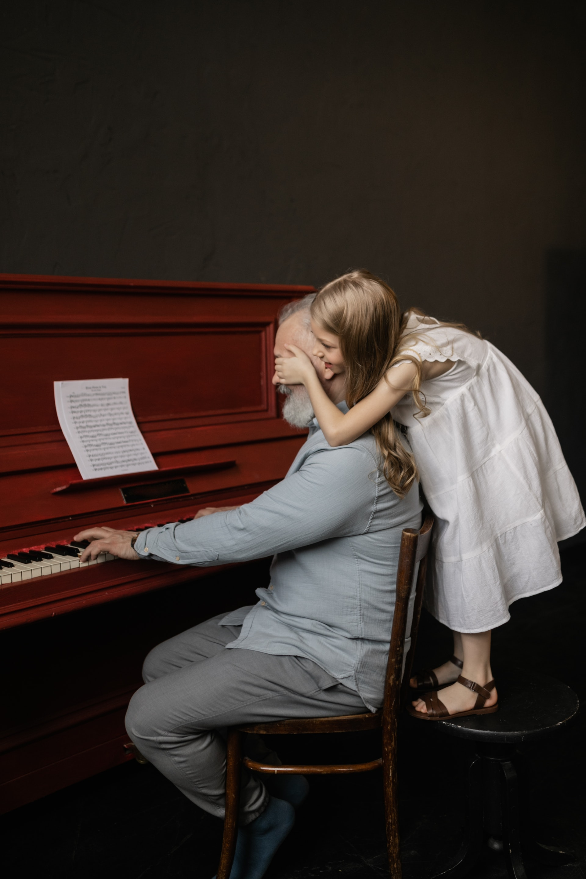 Old man with white beard plays piano with young girl in white dress behind him standing on a stool covering his eyes with her hands.