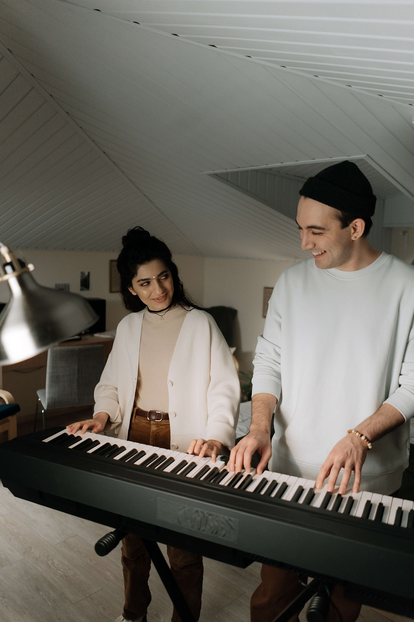 Man and woman playing keyboard together in low ceiling room.