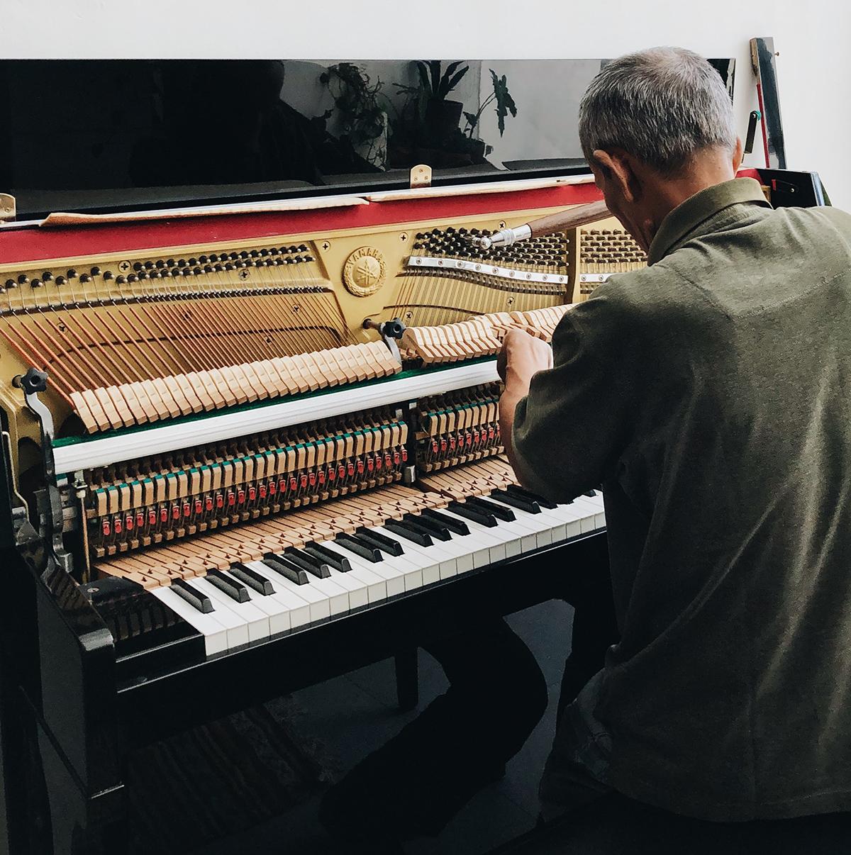 Man tuning upright piano.