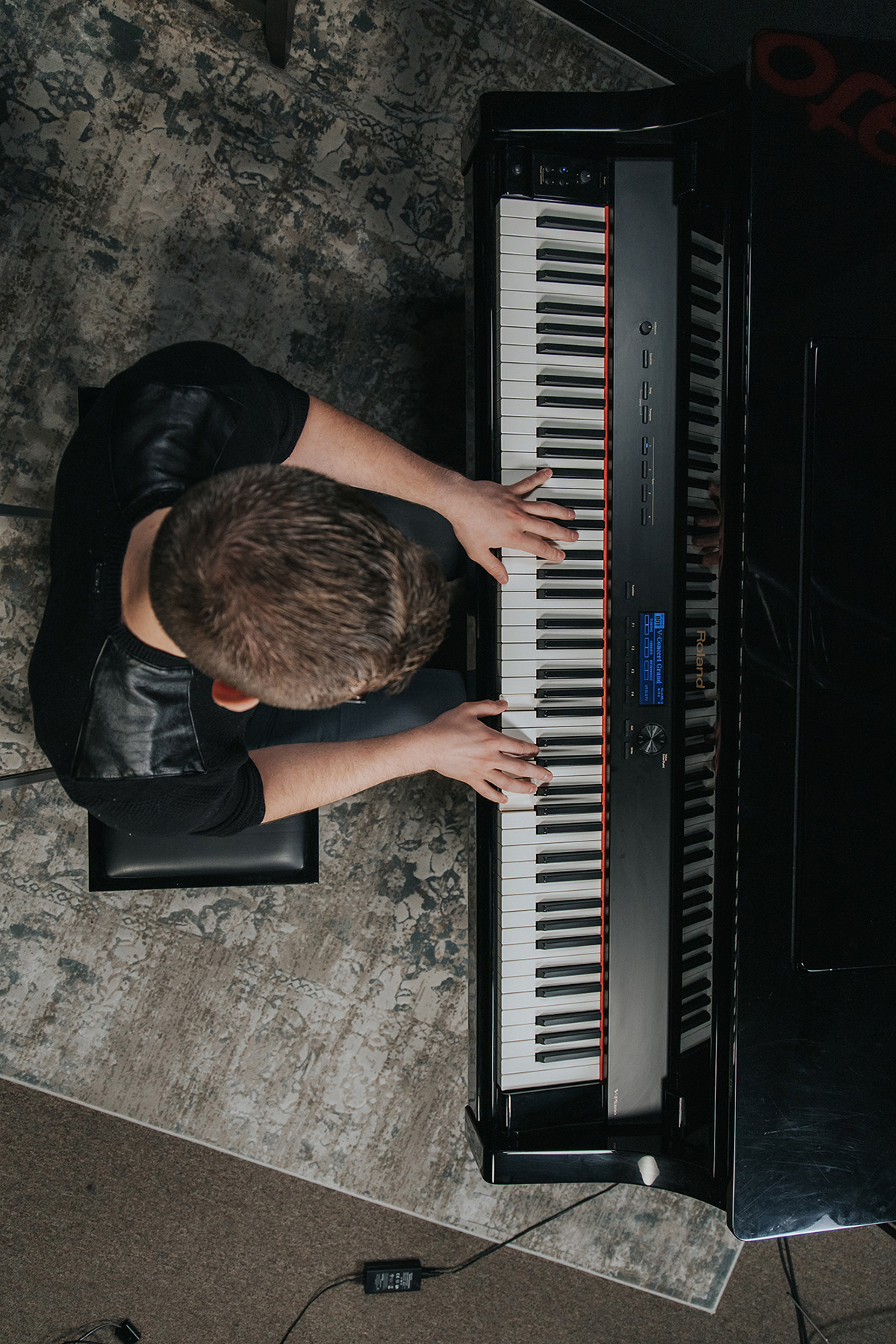 Vertical bird's eye view of Sam (young man with brown hair in black shirt) playing piano.