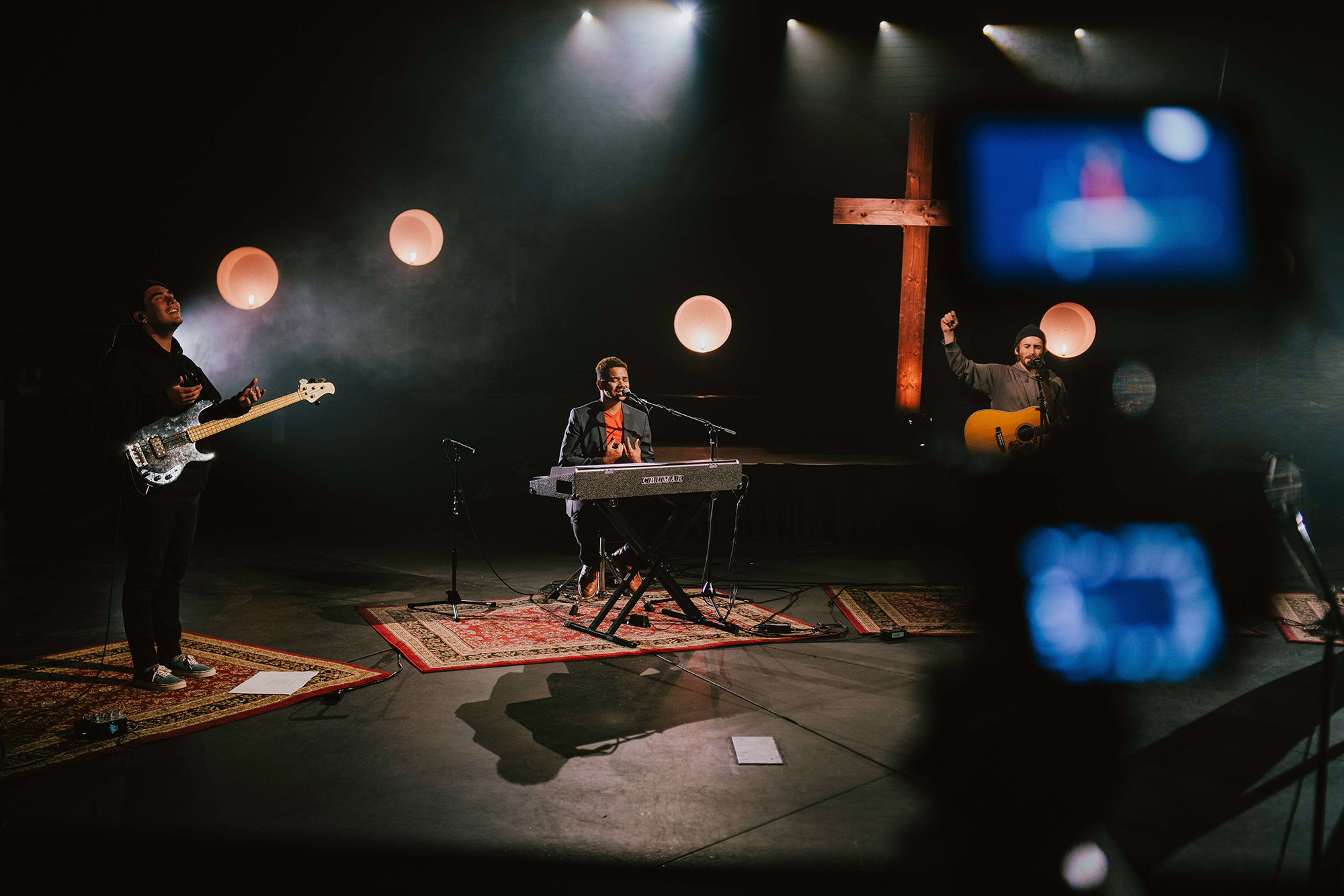Socially distanced worship band in dark studio playing in front of crucifix.  Each band member has their own rug. Left to right: bassist with hands apart in praise, keyboardist singing, acoustic guitarist with one fist raised.