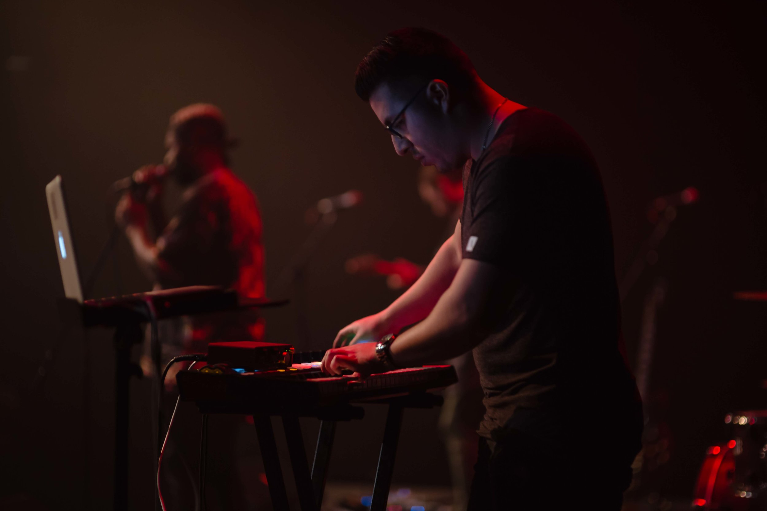 Side view of Kevin Castro (man with short dark hair and glasses) playing keyboard standing up against blurred backdrop of other musicians on a dark stage.