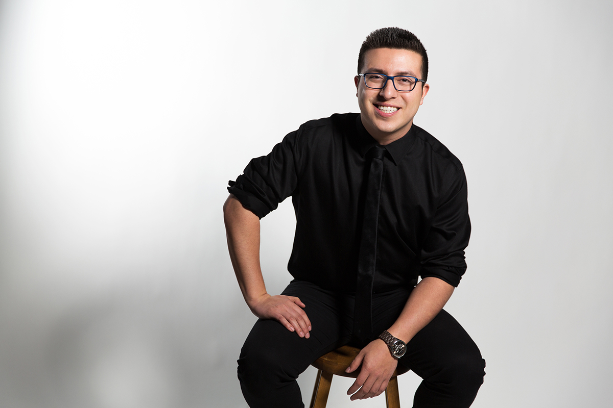 Kevin Castro (man with dark hair and glasses) posing on a stool in black suit, black tie, and black pants against white backgrorund.