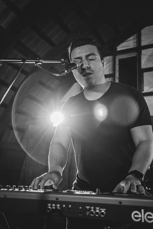Black and white up close photo of Kevin Castro (man with short hair and stubble) playing keyboard standing and sitting into microphone.