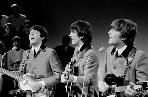 Black and white image of Paul, George, and John performing.