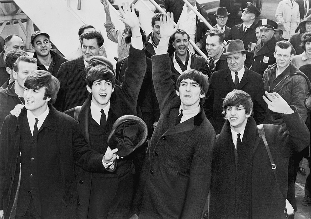 John, Paul, George, and Ringo waving on the airport tarmac with a crowd behind them.