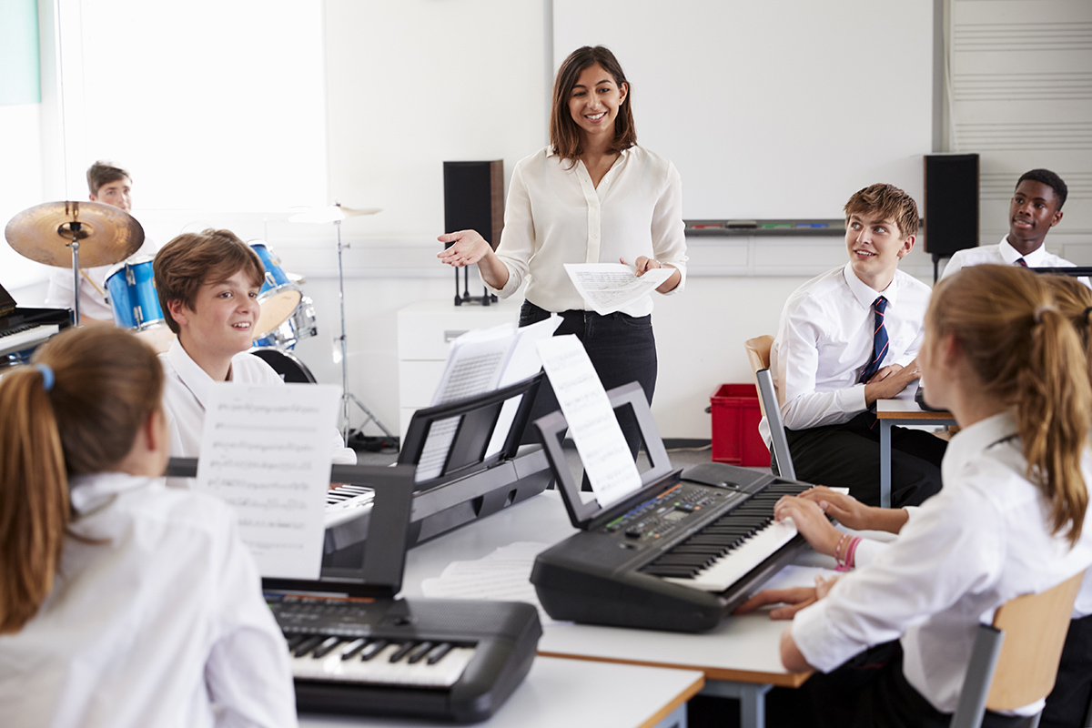 Students playing keyboards in a classroom with female teacher.