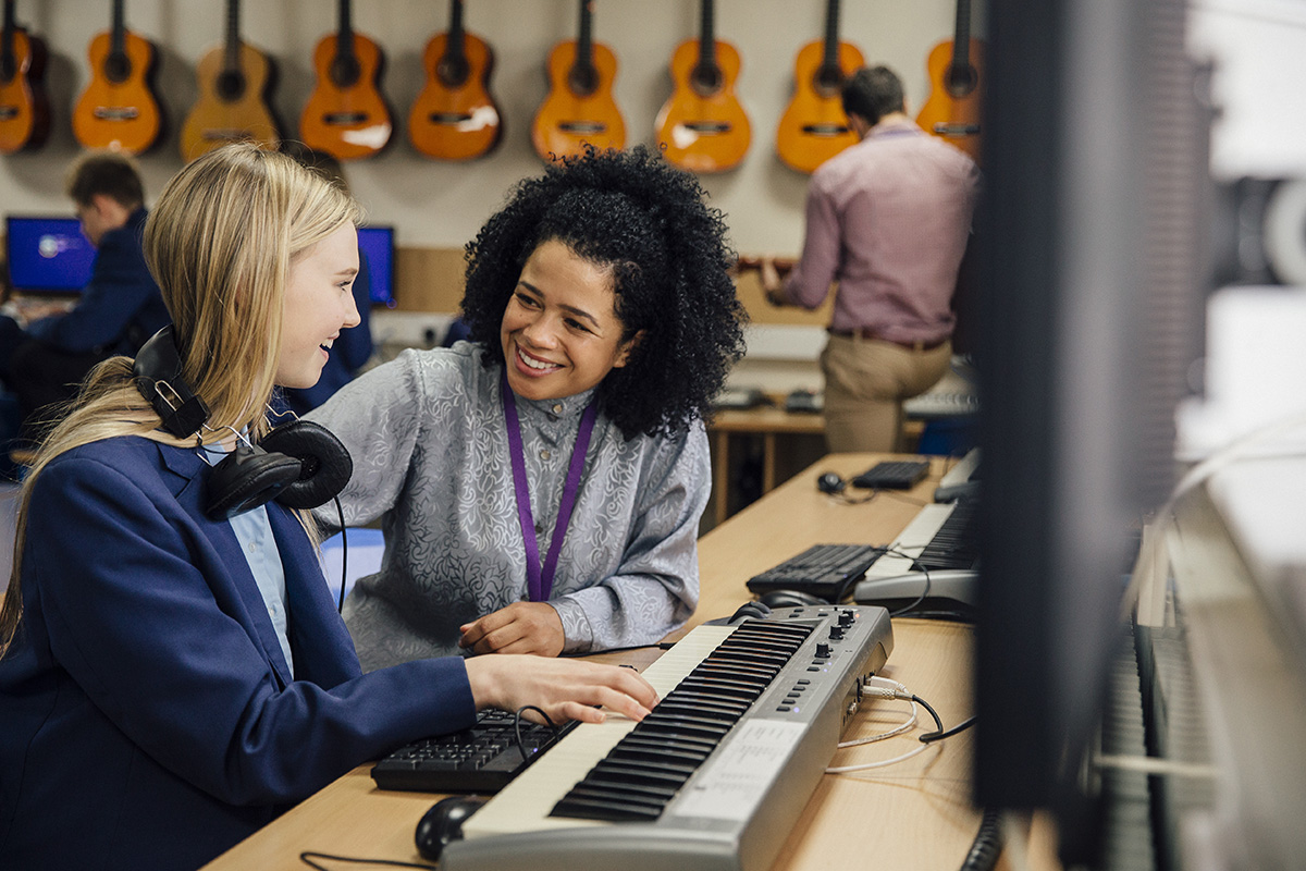 Female teacher is sitting with one of her students in a music lesson at school. She is learning to play the keyboard and is wearing headphones.