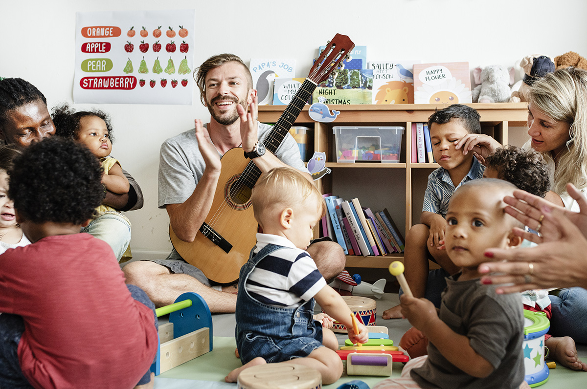 Toddlers and parents playing with musical instruments with male teacher holding a guitar and clapping.