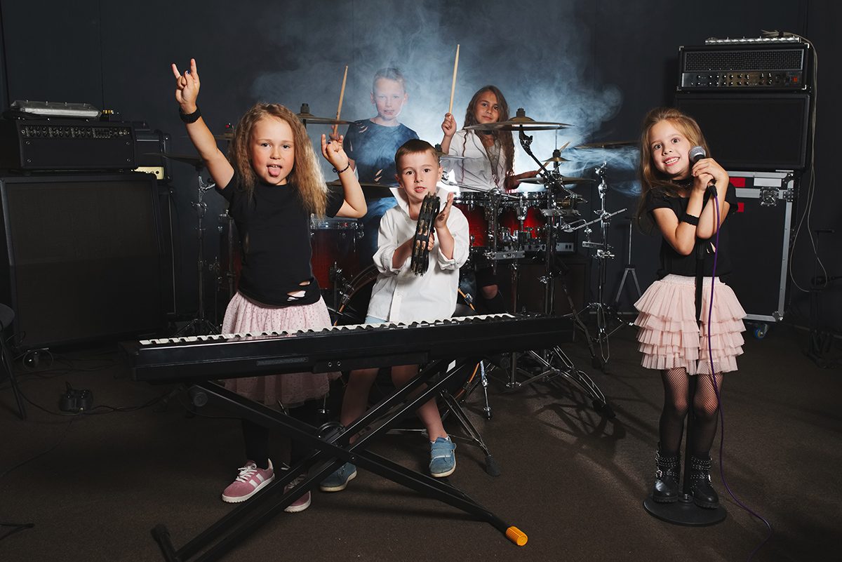 Young children posing with band instruments (keyboard, mic, drum set and amps).