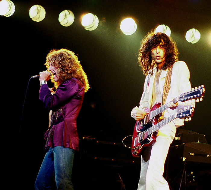 Robert Plant and Jimmy Page on stage. Robert Plant (long curly blond hair) is singing into mic. Jimmy Plant (long brown hair and white suit) is playing double necked gibson guitar.