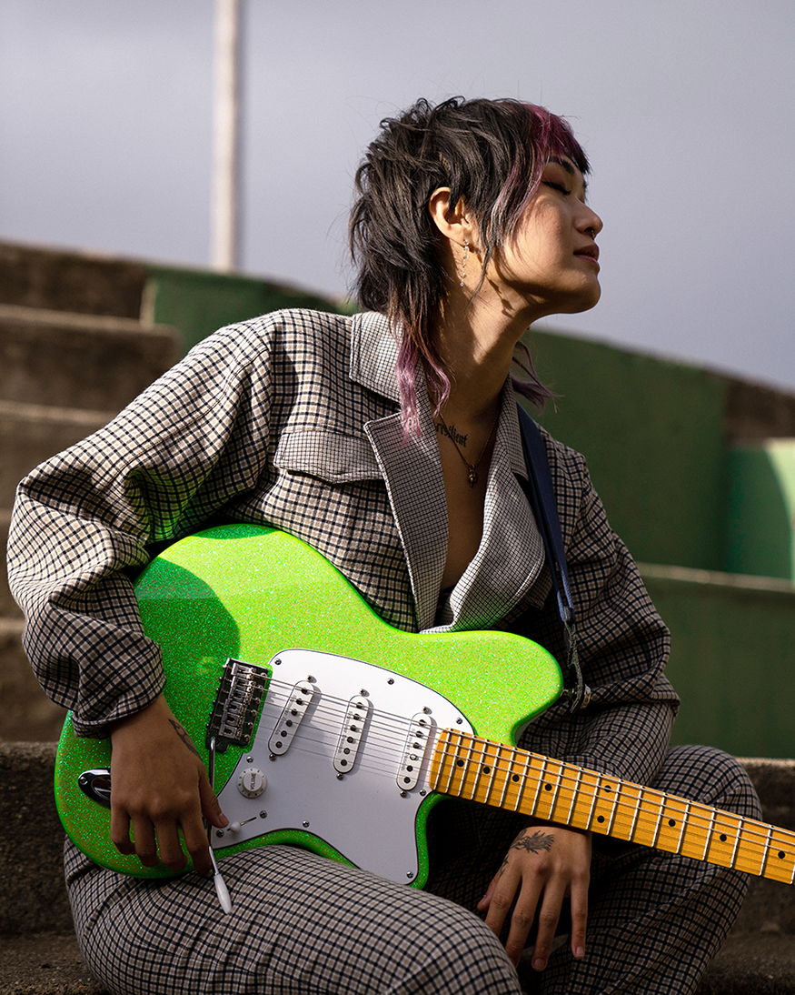 Yvette Young sitting with her guitar - woman with black and violet hair holding green guitar in thoughtful pose wearing checkered jumpsuit.
