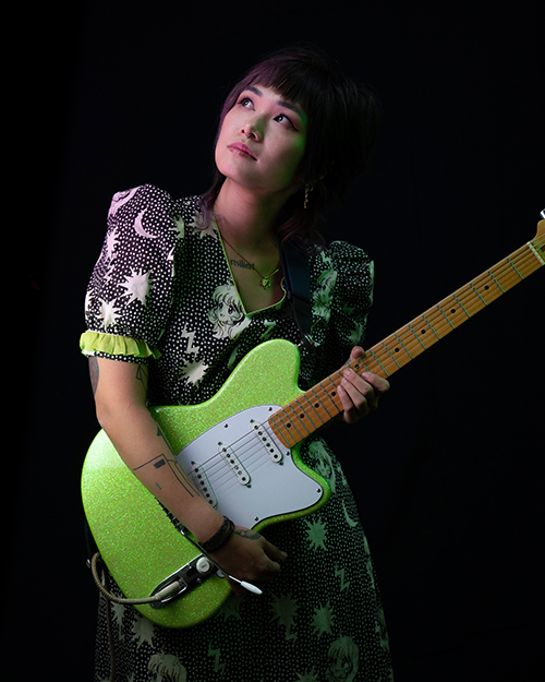 Yvette Young with guitar - dark photo of woman in moon and stars design dress holding green glitter guitar.